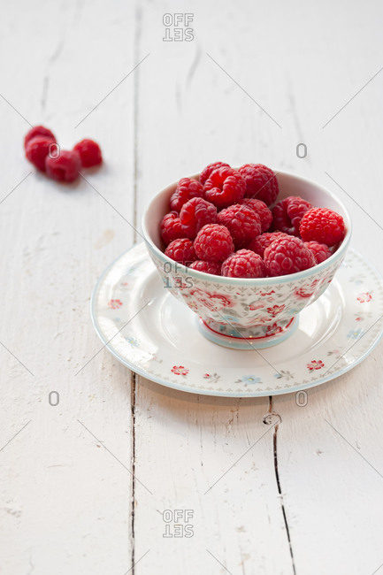 High angle still life composition of porcelain bowl full of fresh ripe red raspberries placed on plate and served on white plank wooden table