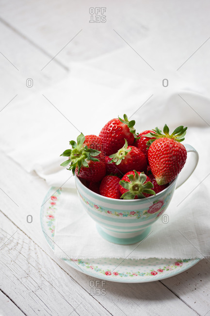 Still life with fresh ripe aromatic red strawberries in porcelain cup with saucer served for breakfast on white wooden table with tablecloth
