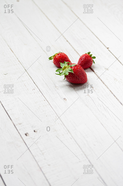 Minimalistic composition with fresh ripe red strawberries arranged on white wooden plank table