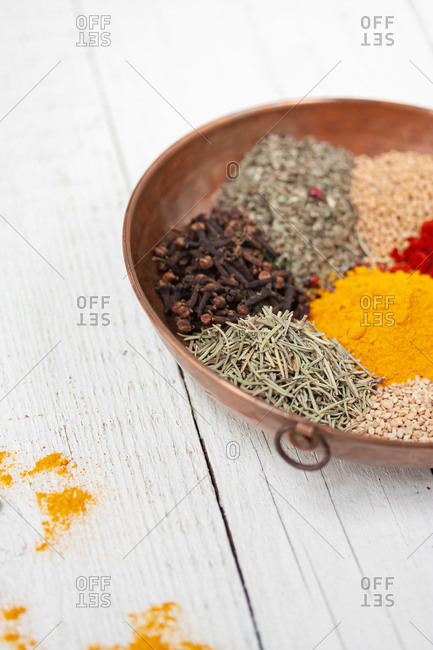 High angle of wooden bowl filled with various types of colorful aromatic dry spices on white wooden table