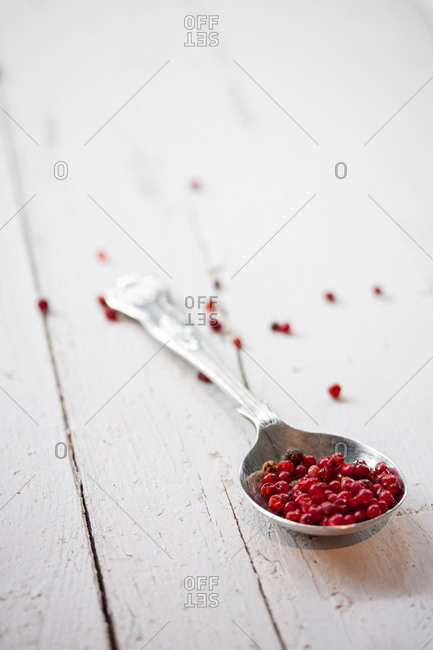 Metal spoon full of dried red peppercorns placed on white wooden plank table with scattered seeds