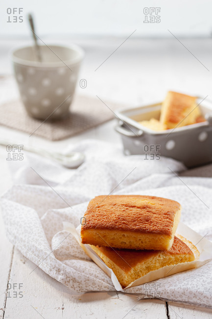 Typical Spanish sobao pasiego cakes served for breakfast with cup of hot drink on wooden table with tablecloth