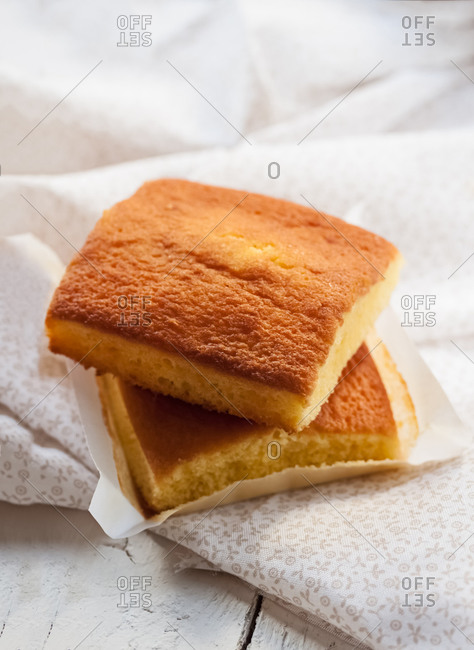 Yummy sweet baked Spanish sobao pasiego cakes served on white wooden table with napkin
