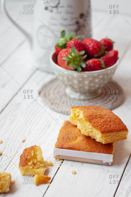 Traditional Spanish sweet sobao cake placed near bowl with fresh ripe strawberries served for delicious breakfast on white wooden table