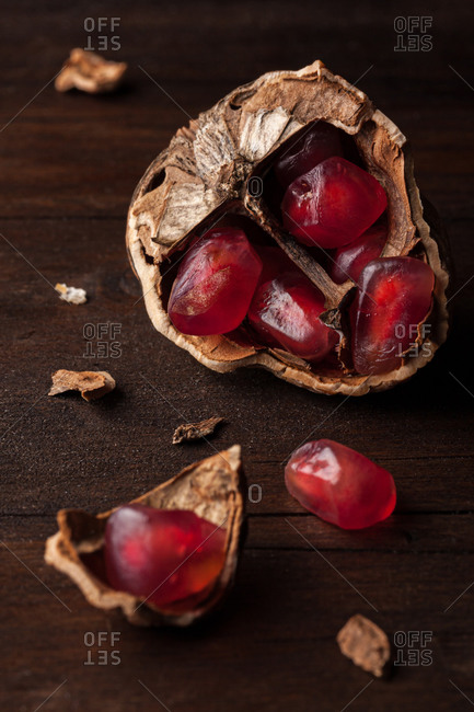 Top view still life composition with ripe red pomegranate seeds arranged in walnut shells on dark wooden background