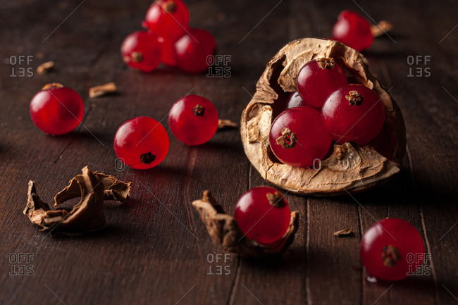 Still life composition with ripe red pomegranate seeds arranged in walnut shells on dark wooden background