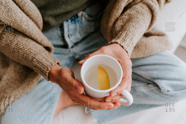 From above of anonymous female sitting with cup of water with slice of fresh lemon in morning at home