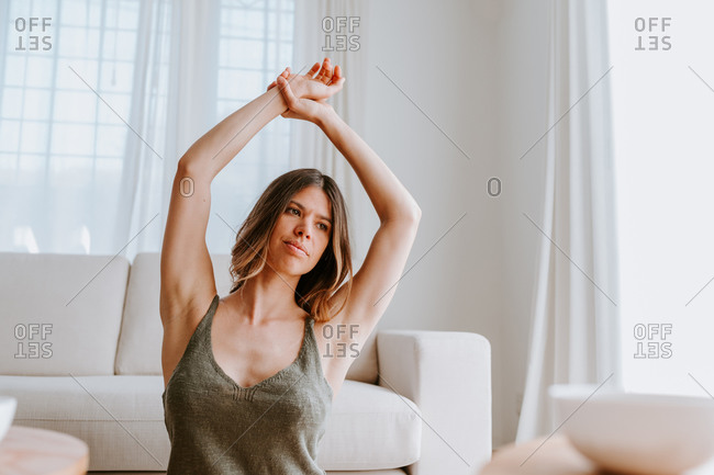 Tranquil female stretching arms while sitting on floor at home and enjoying calm morning while looking away