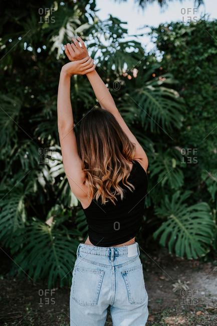 Back view of slender female in casual outfit standing with raised arms and stretching body in tropical garden with green monstera plants