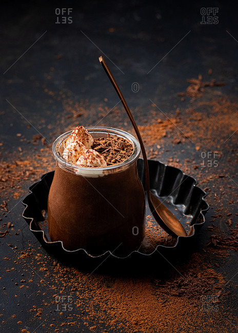 From above tasty chocolate mousse in glass jar arranged on table with chocolate powder dust