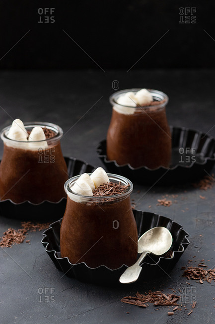 Tasty chocolate mousse in glass jar arranged on table with chocolate powder dust
