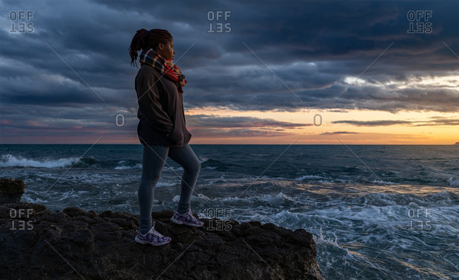 Side view of African American female in warm clothes standing on rocky shore near waving sea and admiring amazing sundown