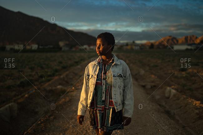 Female tourist lit by sunset sunbeam walking along sandy road in village in highlands