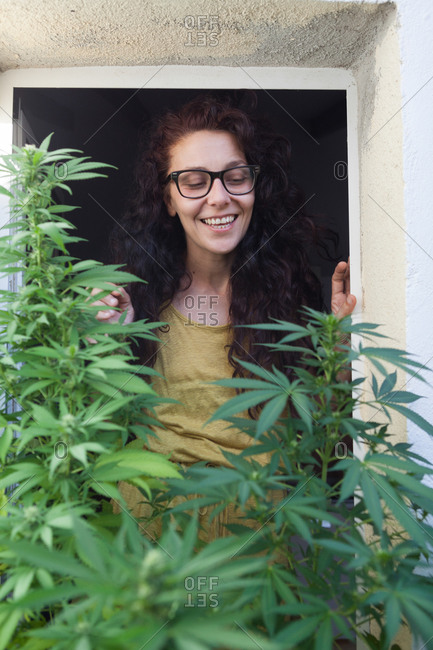 Portrait of woman watching her Marijuana plants