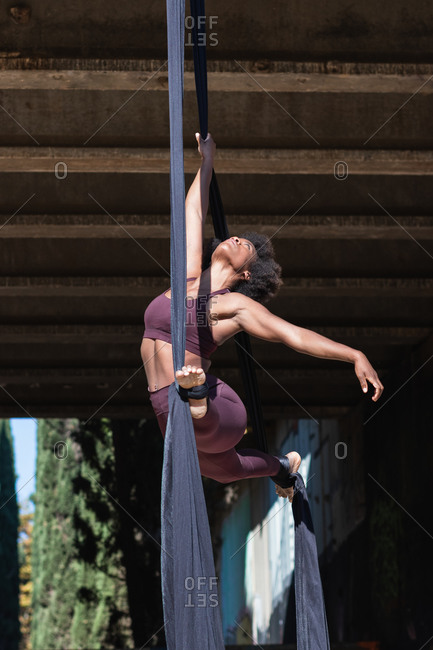 Low angle of flexible African American female doing yoga in aerial silks while performing splits above ground in city