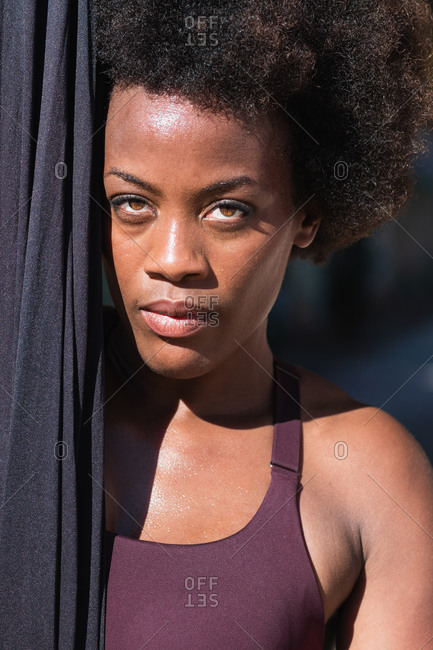 Confident African American female yogi in sportswear standing with hammock while preparing for doing aerial yoga in city