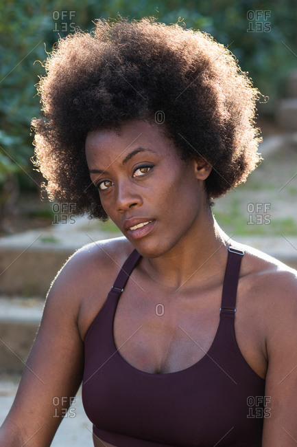 Fit African American female with curly hair and in sportswear sitting on stone stairs on street and looking at camera