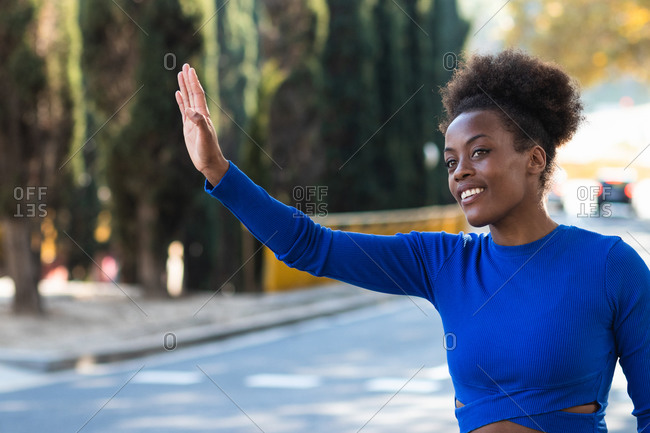 Smiling African American female standing on roadside with outstretched arm and catching taxi