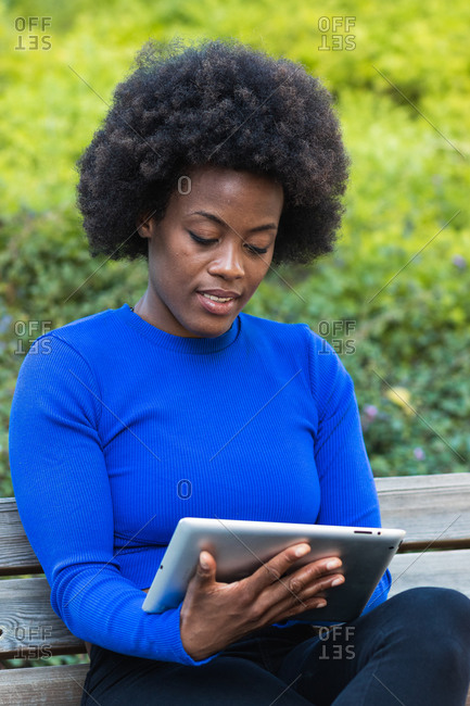 African American female freelancer sitting on bench in park and using tablet while working remotely on startup project