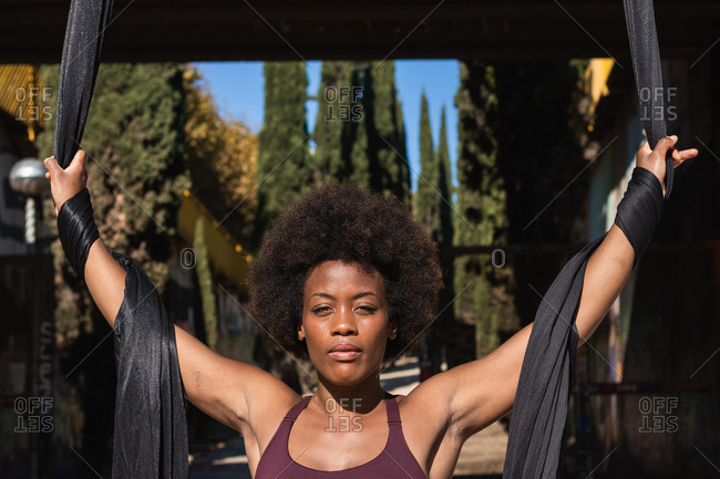 Carefree black female in activewear standing in city aerial silks for aerial yoga and looking at camera