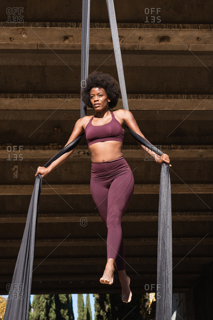 Slender African American female balancing on hanging hammock while doing aerial yoga above ground under bridge in city
