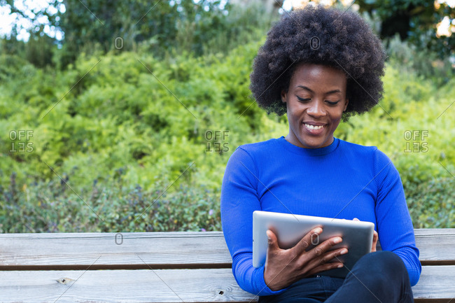 Content African American female freelancer sitting on bench in park and using tablet while working remotely on startup project