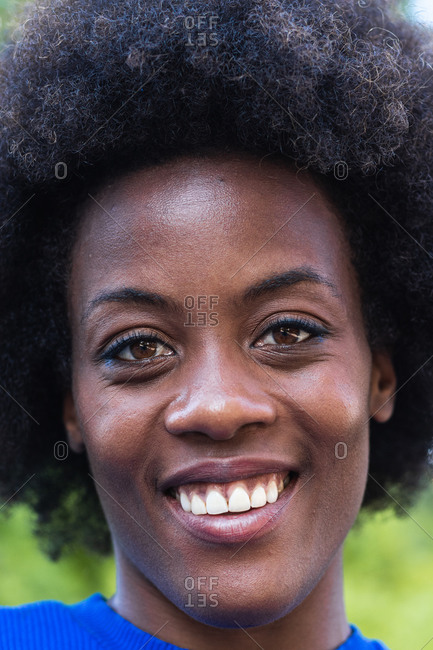 Cheerful black female with Afro hairstyle and charming toothy smile looking at camera