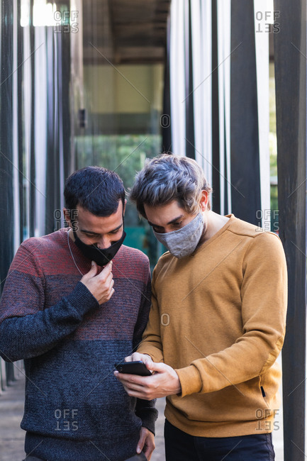 Man in mask sharing smartphone with male friend while standing on street in city