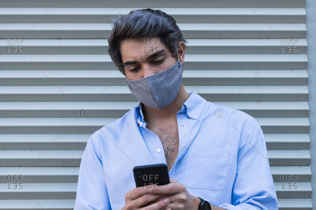 Serious male in stylish clothes and protective mask standing near building in city and texting messages on cellphone during coronavirus outbreak
