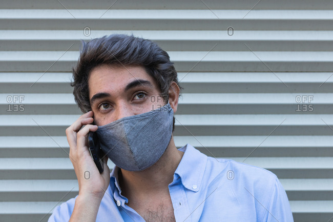 Serious male in stylish clothes and protective mask standing near building in city and talking cellphone during coronavirus outbreak