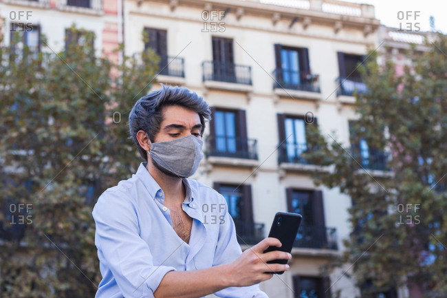 Serious male in stylish clothes and protective mask in city and texting messages on cellphone during coronavirus outbreak