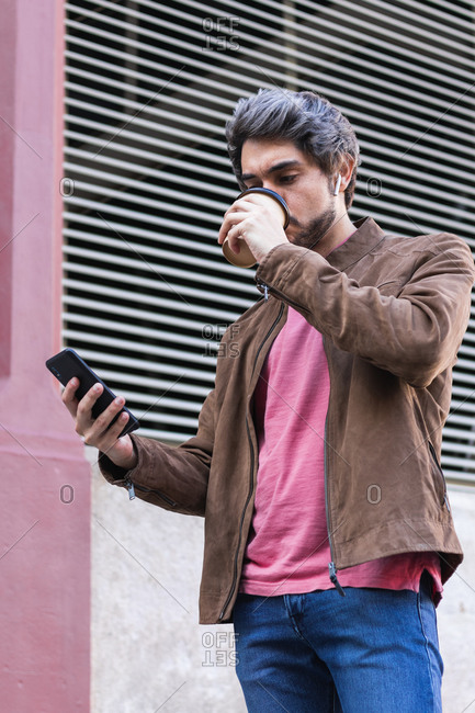 Low angle of stylish male standing on street and drinking coffee to go while surfing Internet on mobile phone