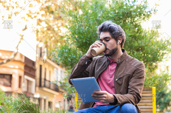 Calm male in casual style sitting in city and enjoying takeaway coffee in paper cup while browsing tablet