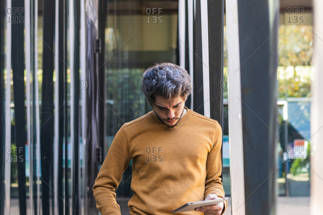 Pensive male standing in city and browsing modern tablet while entertaining at weekend