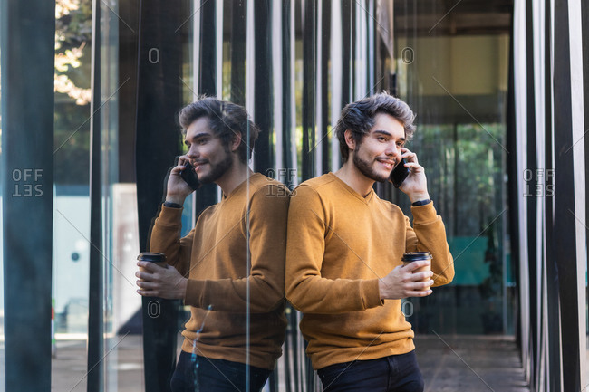 Side view of young male leaning on glass wall of building and speaking on cellphone while standing in city with takeaway coffee in paper cup