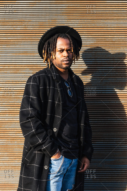 Modern adult black man with dreadlocks wearing hat and stylish coat looking at camera against street wall in sunlight