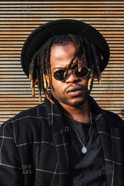 Modern adult black man with dreadlocks wearing hat, sunglasses and stylish coat looking at camera against street wall in sunlight