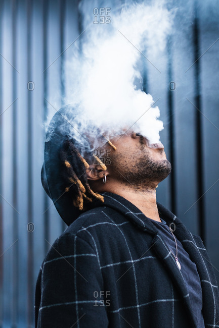 Side view of ethnic back guy with dreadlocks and hat in dense cloud of fume smoking on street in city