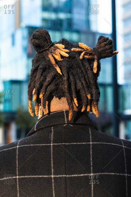 Back view of anonymous African American man with dreadlocks in buns on blurred cityscape