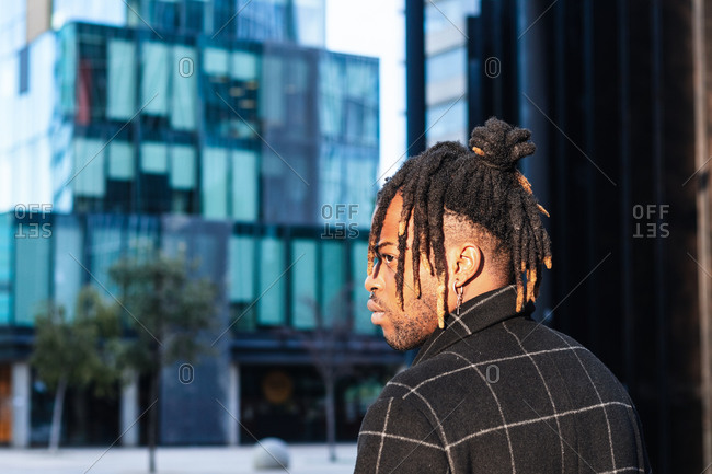 Side view African American man with dreadlocks in buns on blurred cityscape looking away