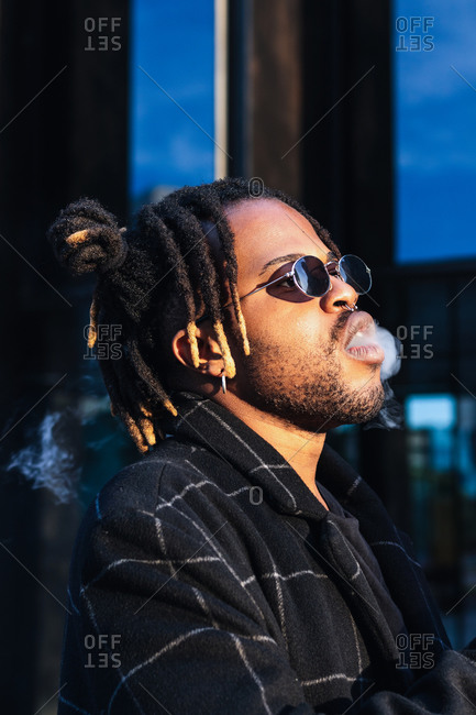 Side view of ethnic back guy with dreadlocks and sunglasses in dense cloud of fume smoking on street in city