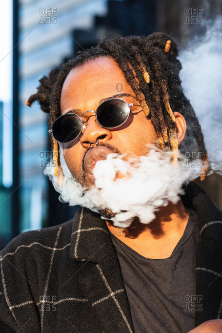 Ethnic back guy with dreadlocks and sunglasses in dense cloud of fume smoking on street in city