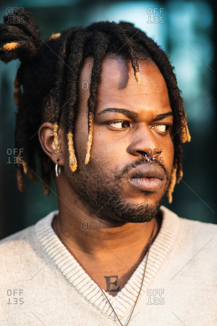 African American man with dreadlocks in bun wearing nose piercing on blurred street background looking away