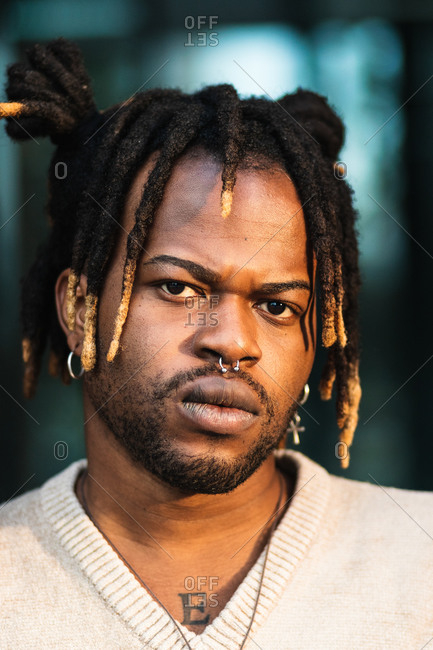 African American man with dreadlocks in bun wearing nose piercing on blurred street background looking at camera