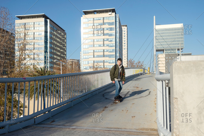 Full body of modern teen male student in warm clothes skateboarding on pedestrian bridge in city in sunny day