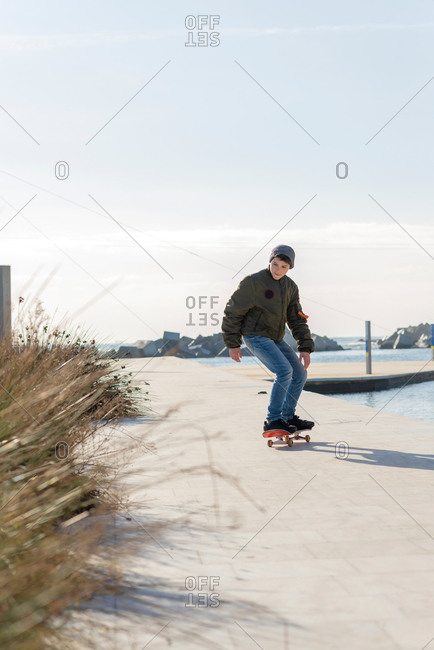 Full body of active male skater in warm jacket and jeans performing trick on skateboard on paved walkway near river