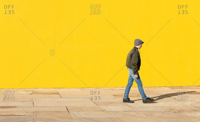 Full body side view of teen male wearing casual warm jacket with jeans and hat walking on pavement against bright yellow wall on street
