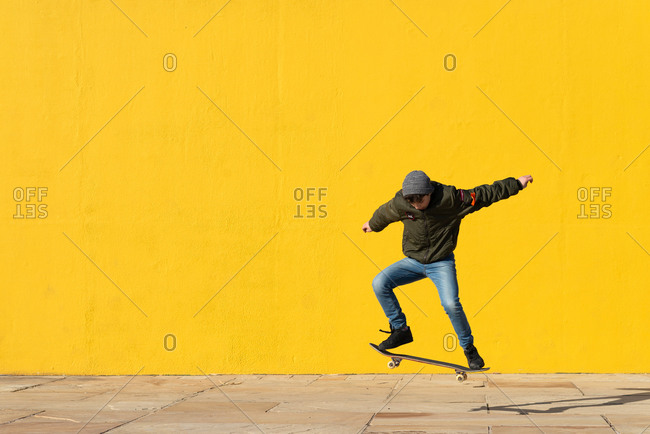 Full body of active male teenager in warm outfit performing trick on skateboard and jumping above paved street against bright yellow wall