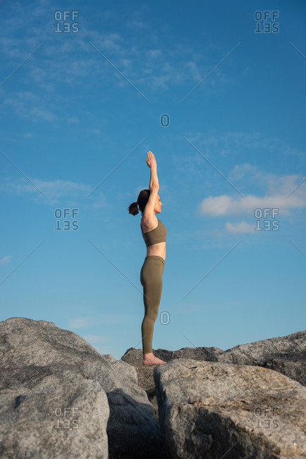 Side view of young female in warm activewear standing in Mountain pose with arms up while practicing yoga on rock against blue sky