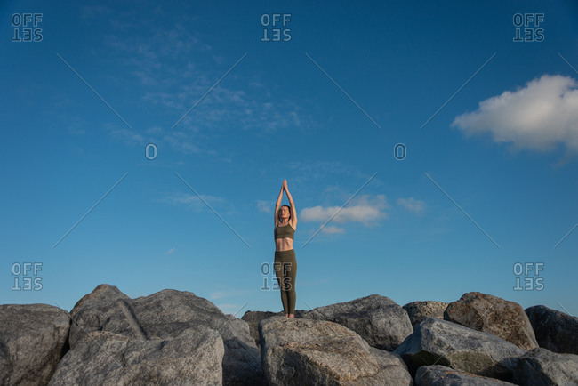 Young female in warm activewear standing in Mountain pose with arms up while practicing yoga on rock against blue sky